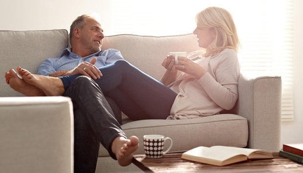 Couple has conversation while drinking tea together on couch