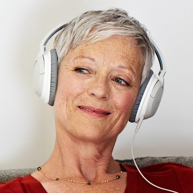 Mature woman wearing headphones looks off to the side with a smile.