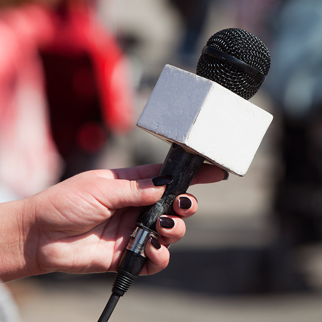 A woman holds a press microphone as though she is interviewing someone