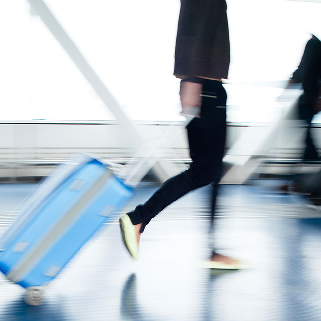 Blurry image shows person walking pulling luggage.