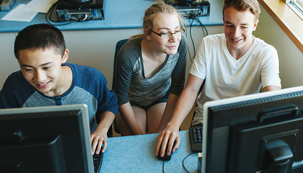 Three youth work on two computers. One looks over the shoulder of another.