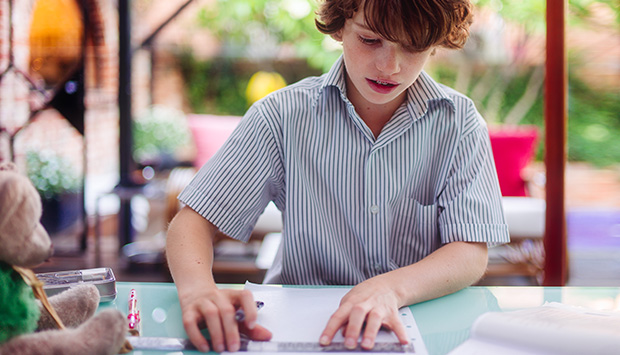 Boy holds a ruler against lined paper.