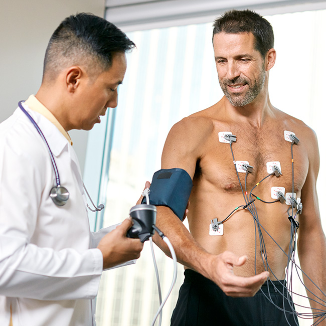 Physician monitors his patients blood pressure and heart rate during an advanced test.