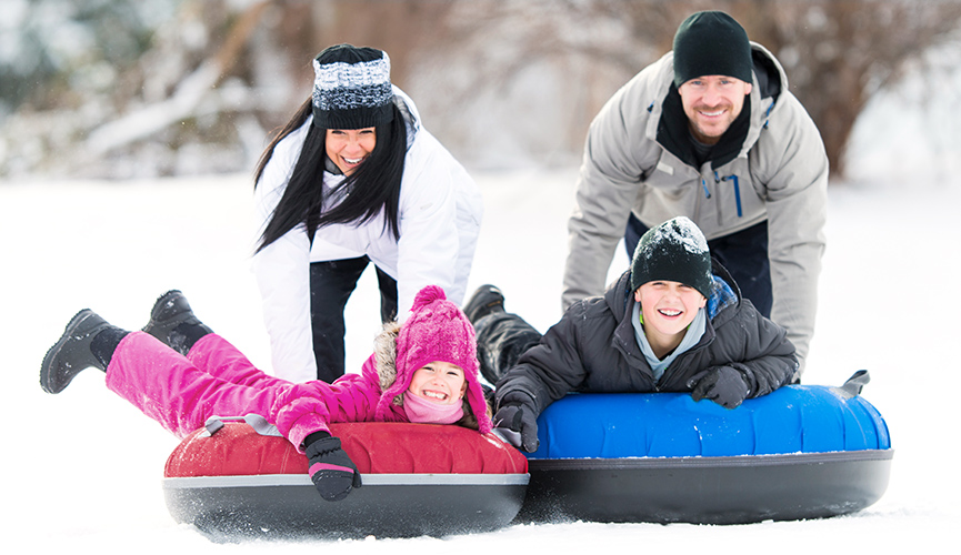 A happy, healthy, family of four plays on snow tubes in the winter.