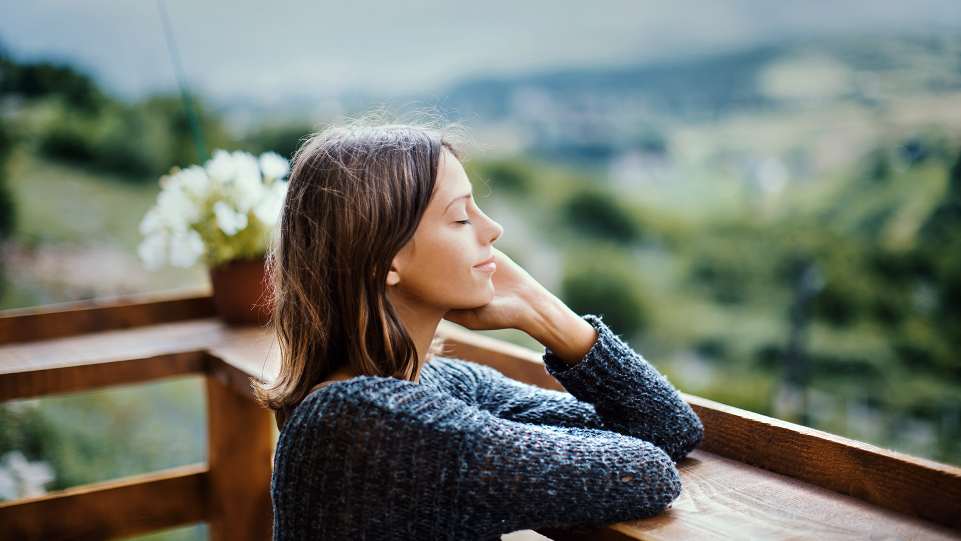 Woman at a table in front of a window overlooking a greenery smiles with her eyes closed and her hand against her face.