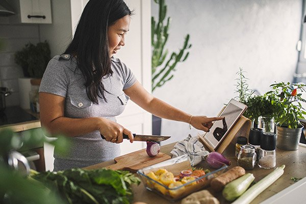 Woman in her kitchen making a delicious, healthfull meal with the help of an online recipe.