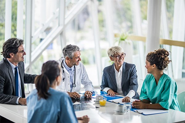 A physician in a lab coat sits in a board room with executives.