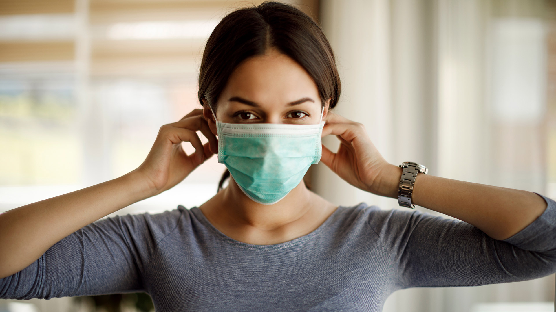 Woman in a grey shirt places a mask on her face as a preventitive measure against COVID-19.
